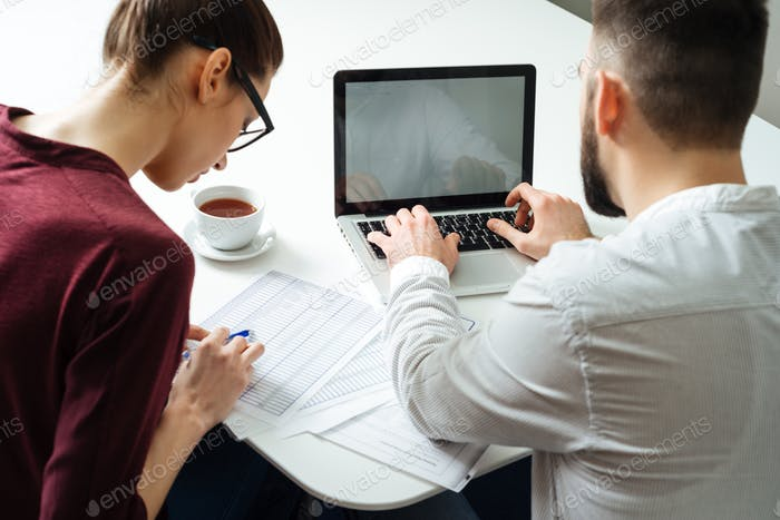Back view of two focused serious businesspeople using laptop