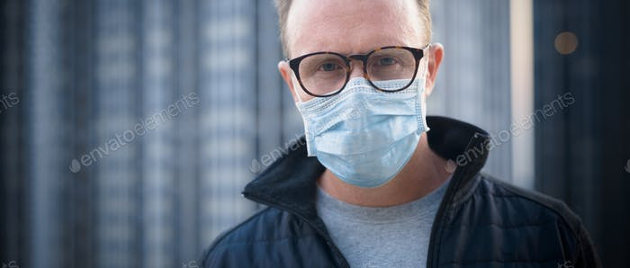 Mature man with mask for protection from corona virus outbreak and pollution in the city