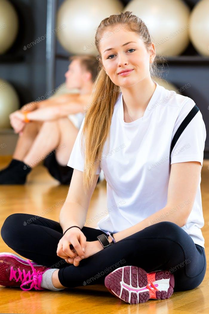 Smiling Woman Sitting Cross Legged In Fitness Center