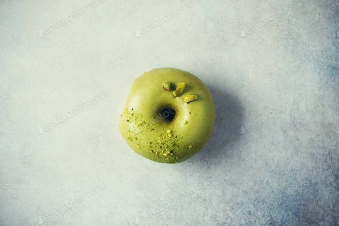 Sweet doughnut with green glaze and pistachio on grey background. Tasty donut on pastel concrete