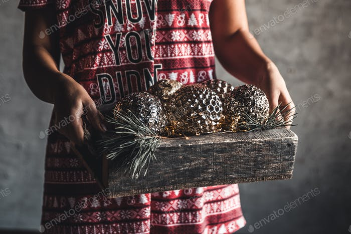 Girl in a Christmas dress holds balls in a wooden box, holiday, comfort