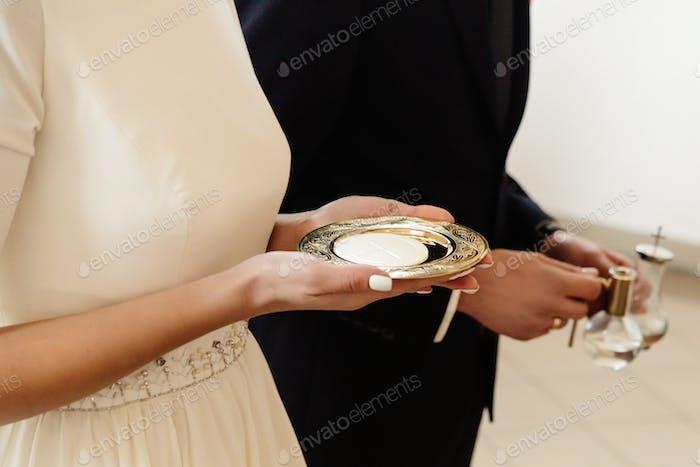 Hände von Braut und Bräutigam Vorbereitung auf die Kommunion bei der Hochzeitszeremonie in der Kirche