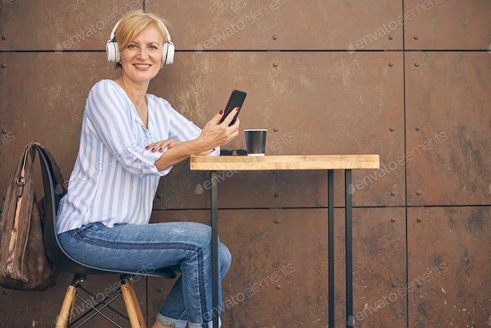 Joyful woman with a smartphone looking forward