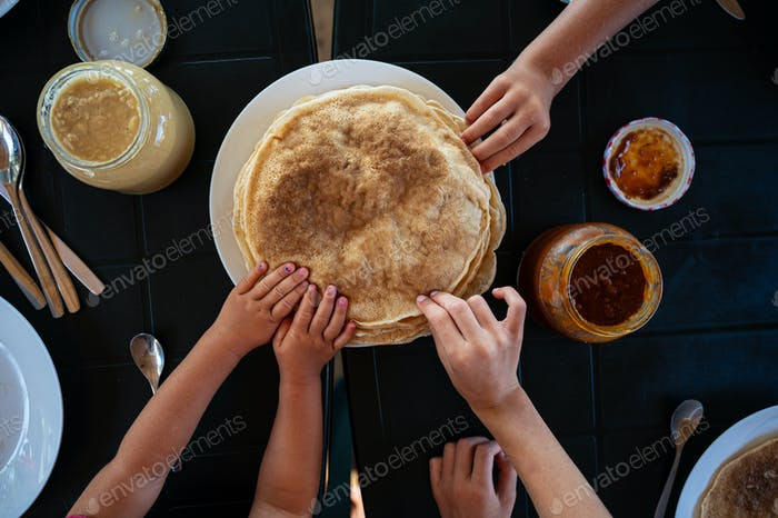 Kids reaching for crepes at breakfast