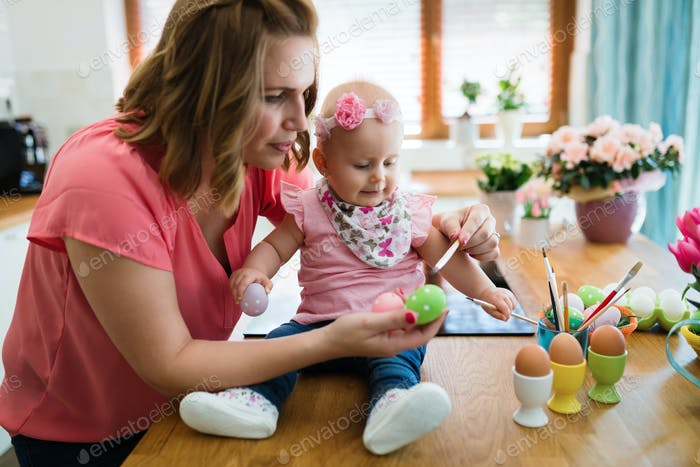 Mother and child painting colorful eggs