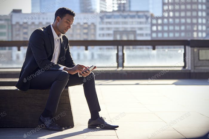 Millennial black businessman sitting on the Thames embankment, London, using smartphone