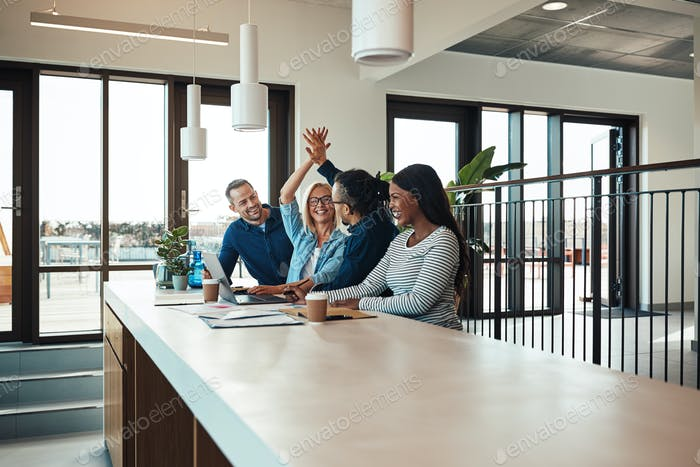 Two laughing coworkers high fiving together during an office meeting