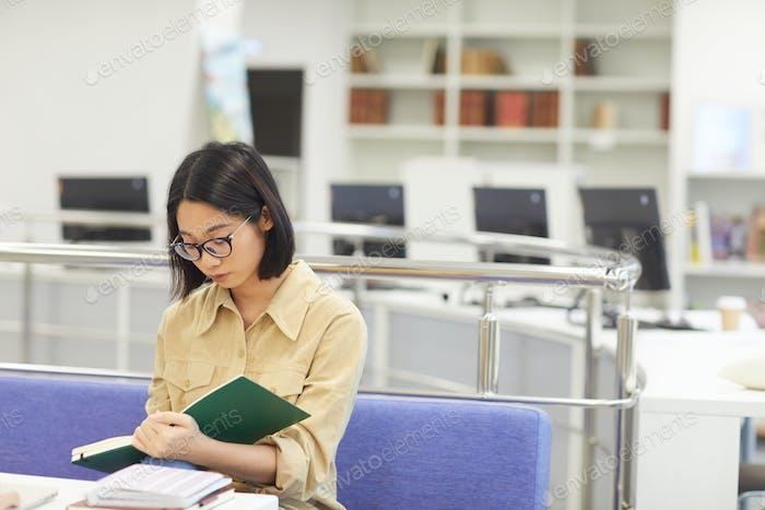 junge asiatische Frau Lesen in Bibliothek