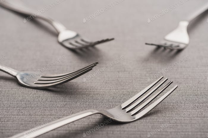 Selective Focus of Shiny Forks of Grey Tablecloth