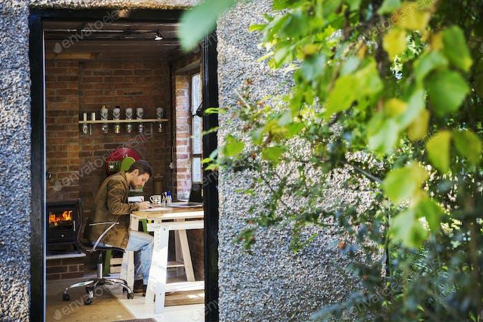 Blick durch eine offene Tür, ein Designer sitzt in seiner Lederwerkstatt an einem Schreibtisch, Zeichnung.