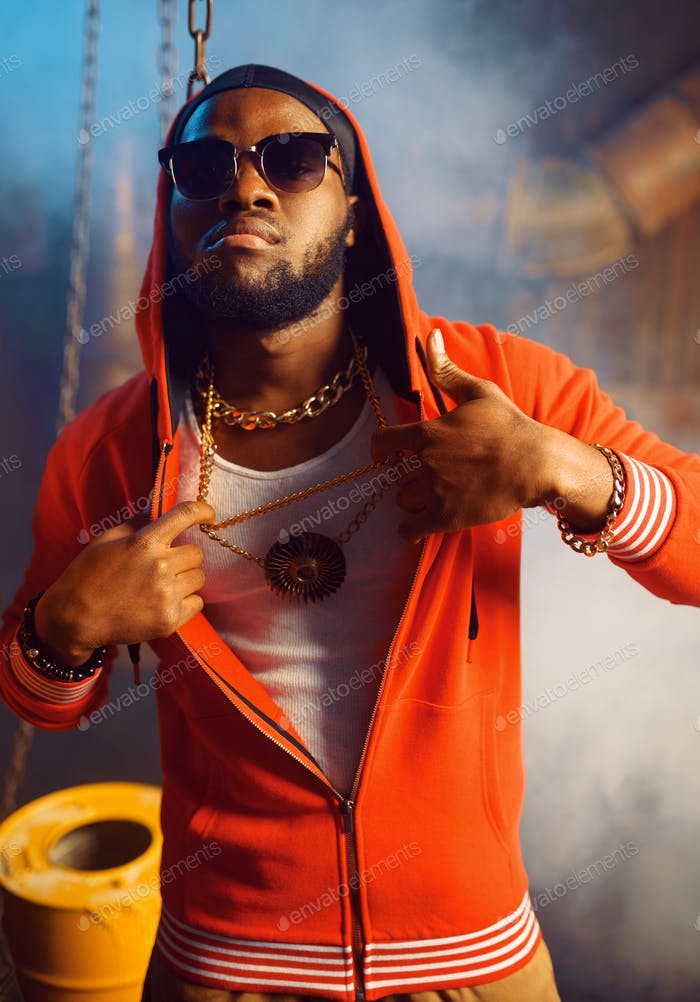 Rapper in red hoodie and sunglasses in studio