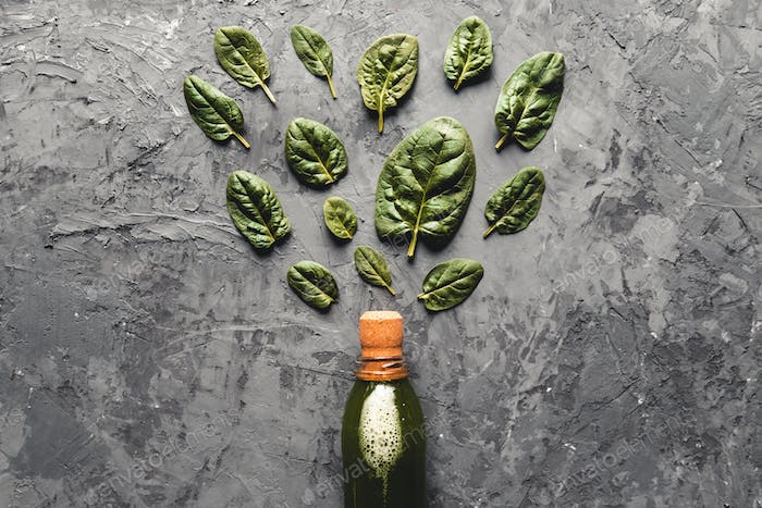 Spinach smoothie in the bottle. Fresh spinach in wooden plates. Useful food, eco, vegan