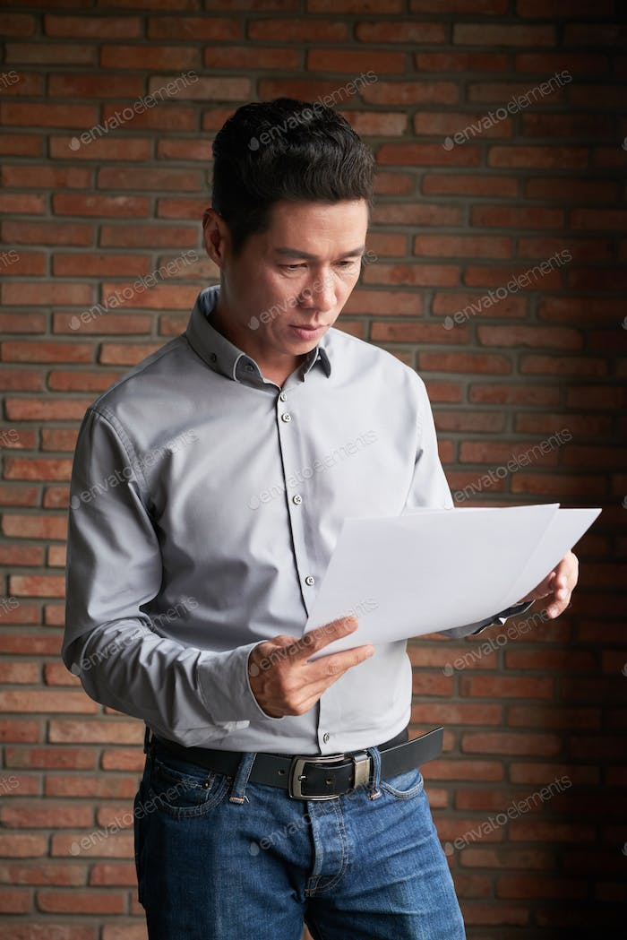 Asian Businessman Studying Documents