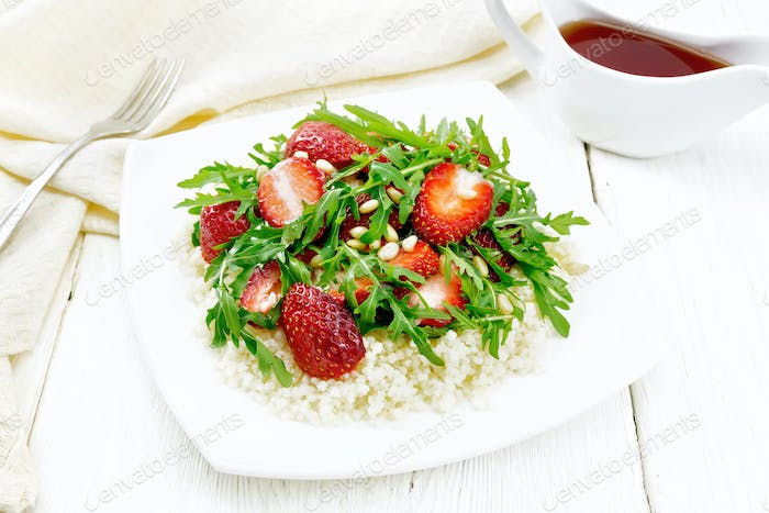 Salad of strawberry and couscous on wooden board