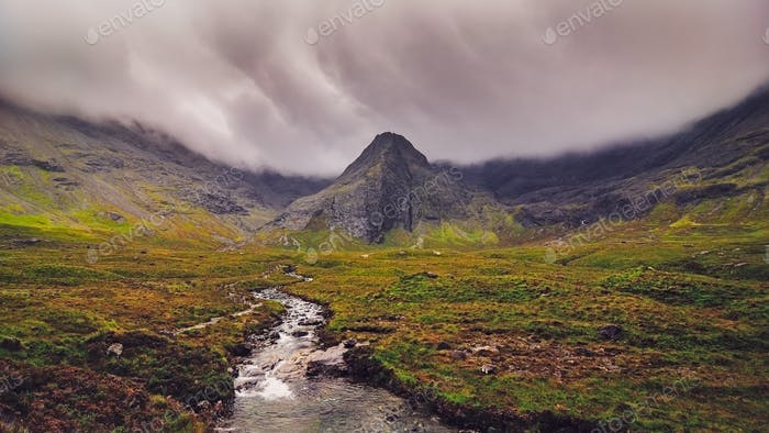 Moody landscape view of Cuillin hills with river in foreground, Scotland