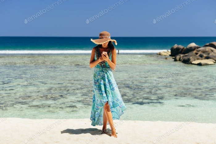 woman holding smartphone on beach