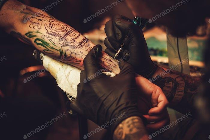 Татуировка художник делает татуировку на руке мужчины.