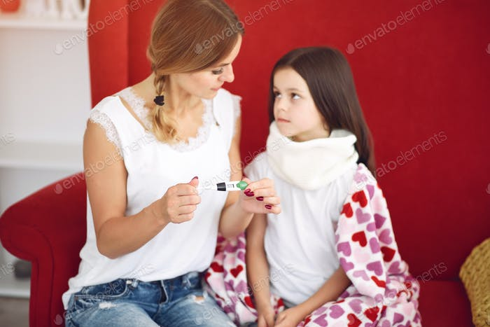 Mom measures the temperature of her ailing daughter