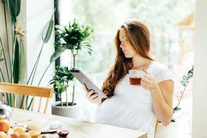 Junge moderne schwangere Geschäftsfrau, die beim Frühstück auf einer Tablette arbeitet.