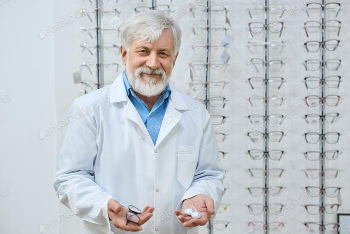Expirienced old doctor helping to choose eyeglasses