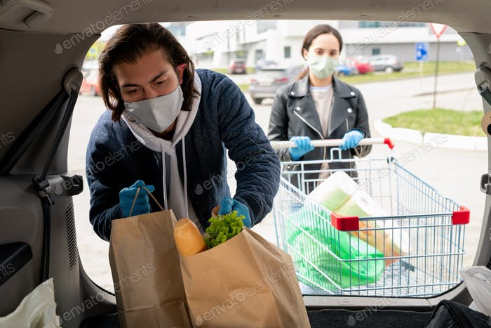 Young man in protective gloves and mask putting paperbags into car trunk