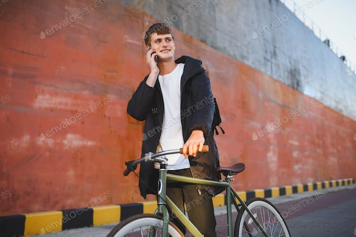 Man with brown hair walking with classic bicycle happily looking aside talking on his cellphone