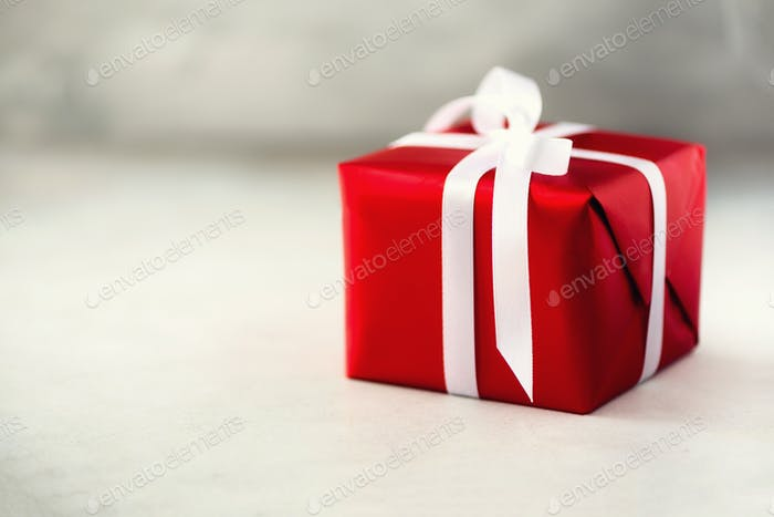 Red gift box on grey concrete background, copy space. Christmas, new year, birthday party, valentine