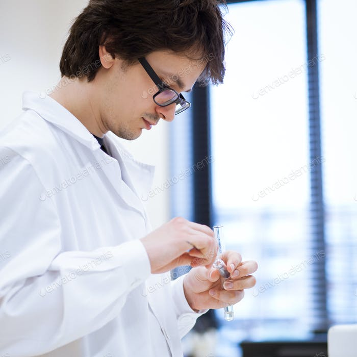 young, male researcher/chemistry student carrying out scientific