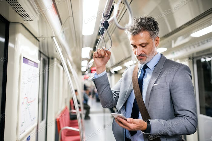 Mature businessman with smartphone in a metro train.