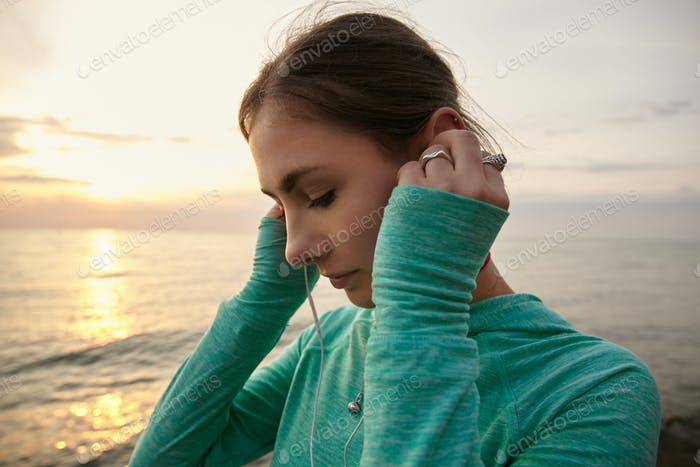 Horizontal photo of young woman at the seaside in the morning, listening favorite music