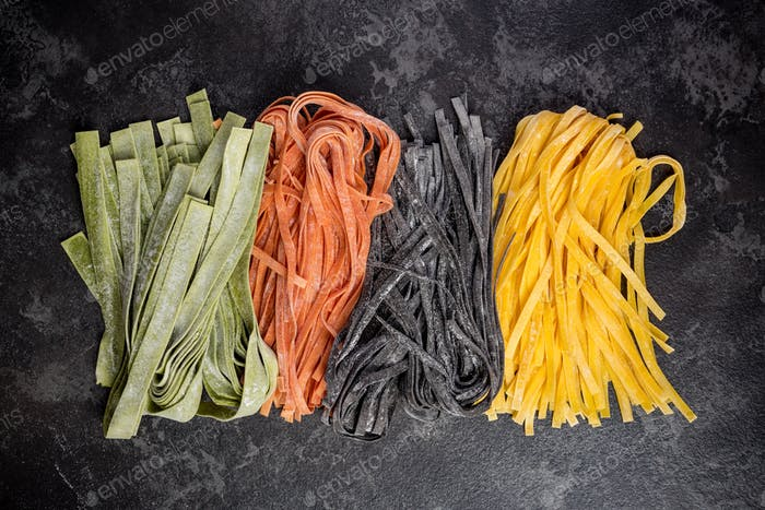 Homemade uncooked colorful tagliatelle pasta