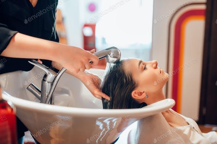 Hairdresser washes customer hair in basin