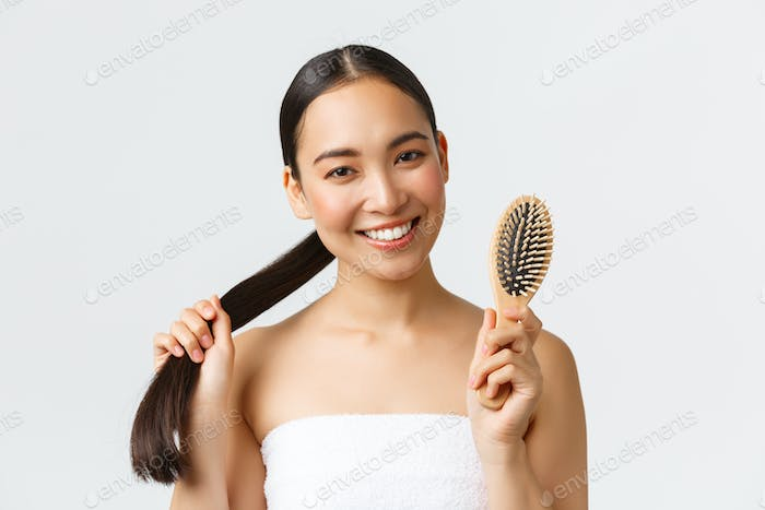 Beauty, hair loss products, shampoo and hair care concept. Close-up of happy attractive asian woman