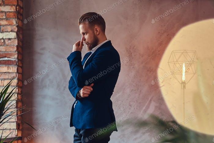Человек в элегантном костюме в комнате.