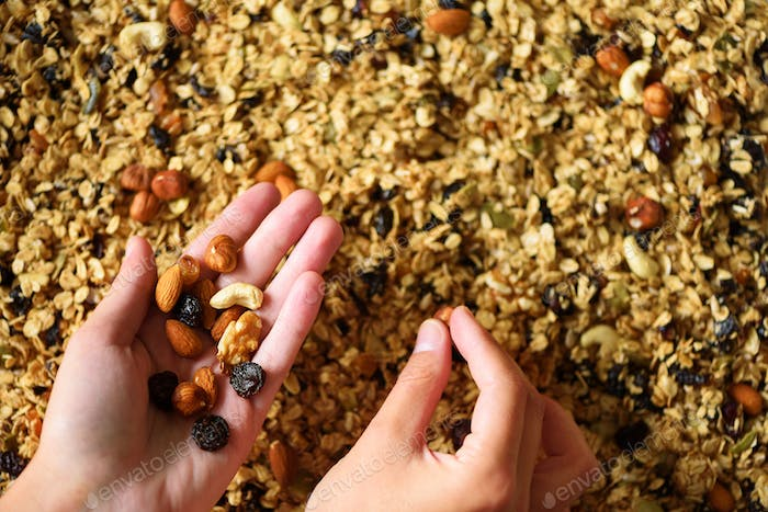 Female hand holds granola against the background of baking sheet with granola. Food for breakfast