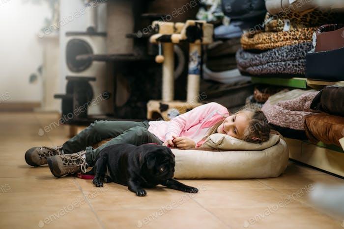 Маленькая девочка с щенком спят в зоомагазине