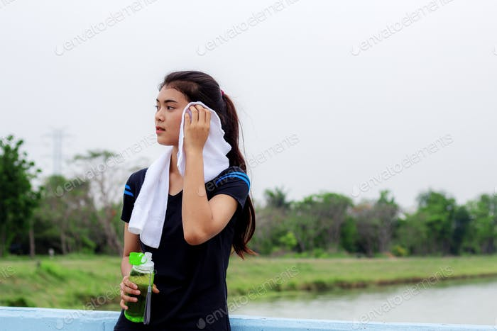 Girl is wiping sweat in park