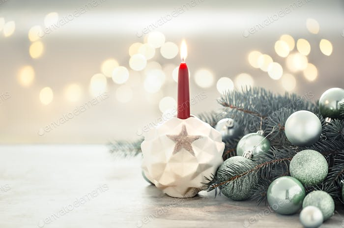 Christmas holiday background with a candle in a candlestick.