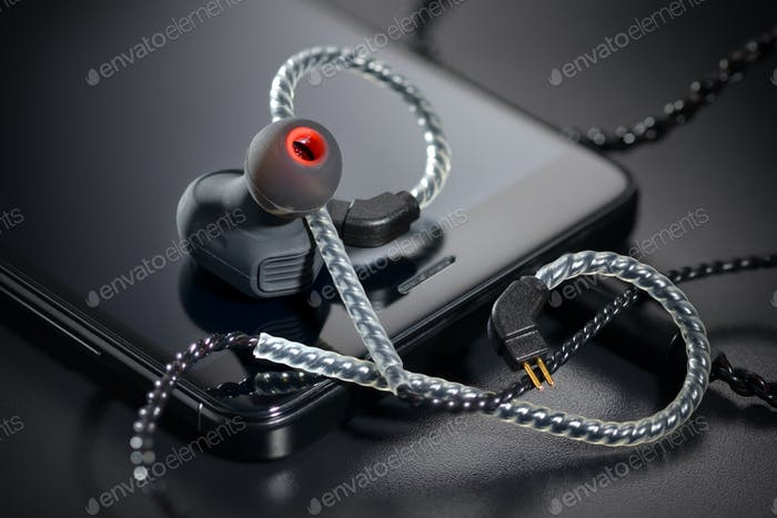 Black earbuds and smartphone