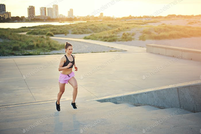 Fit young woman jogging up a flight of stairs
