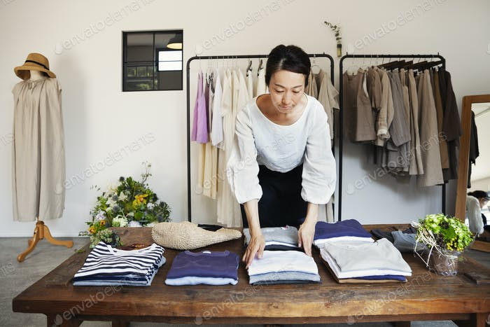 Japanese woman standing in a small fashion boutique, arranging T-Shirts on a coffee table.
