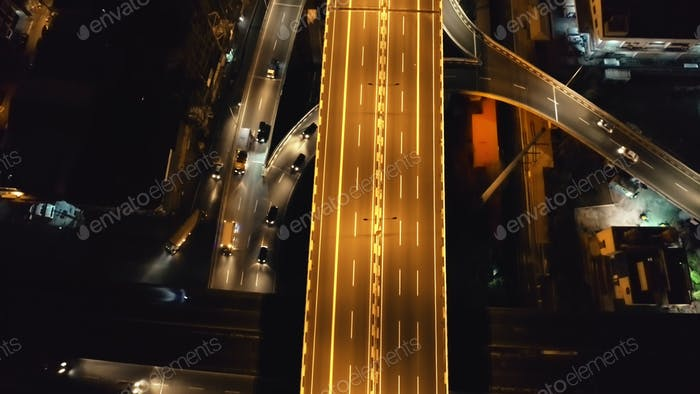 Closeup traffic road with cars, trucks drive at night top down aerial view. Philippines capital town