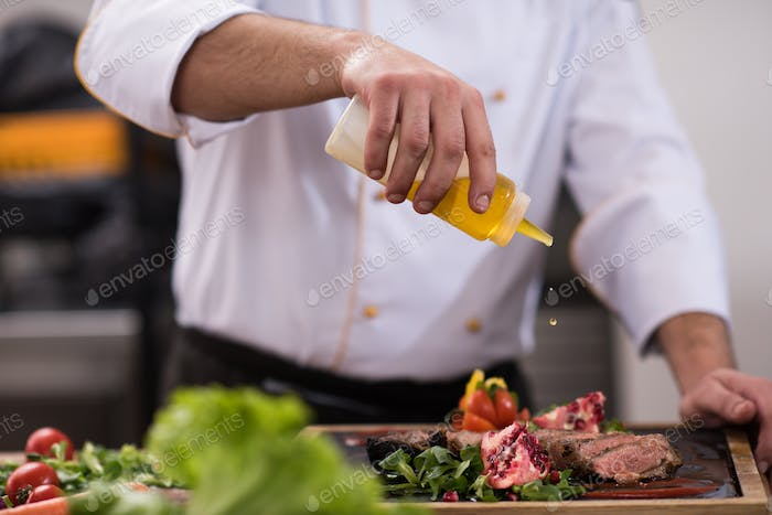 Chef finishing steak meat plate