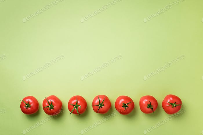 Row of fresh red tomatoes on green background. Top view. Copy space. Minimal design. Vegetarian