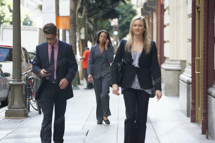 Gruppe der Geschäftsleute zu Fuß entlang Straße