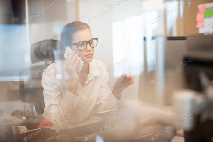 Businesswoman talking on mobile phone at office