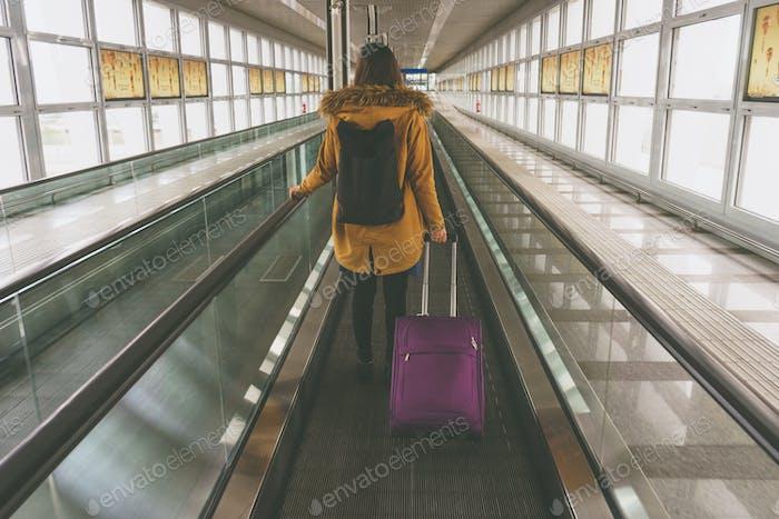 Junge Frau mit Handgepäck auf Reisebegleiter auf internationaler Luft