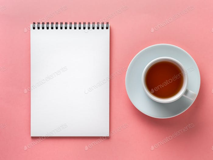Blank notepad white page  and cup of tea on pink desk, color background. Top view,  flat lay.