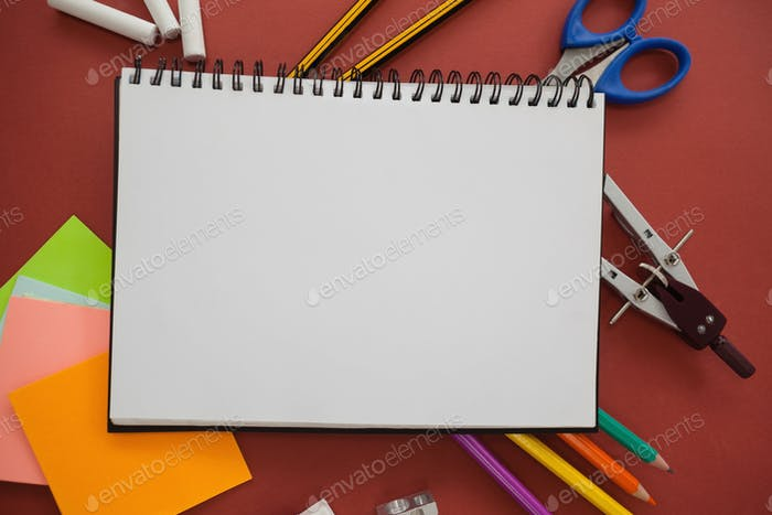 Various school supplies arranged on red background