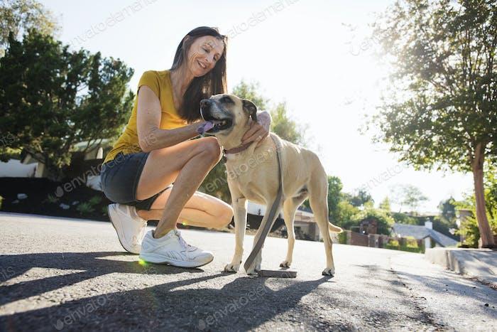 Senior woman wearing shorts, kneeling in the street, stroking a dog.